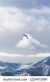 Sky gliding in winter snowy mountains at nice sun evening. Caucasus Mountains, Georgia, region Gudauri.