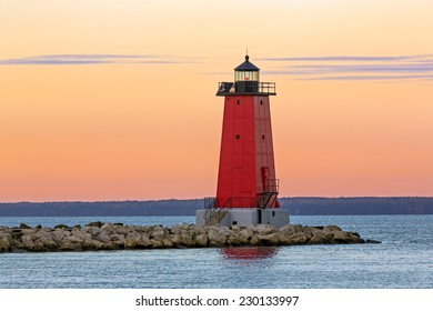The sky glows with color as the sun rises on the red lighthouse at Manistique on the Lake Michigan Coast of Michigan's Upper Peninsula.