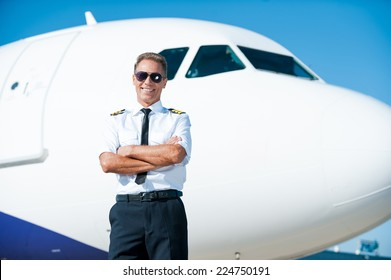 Sky is my passion. Confident male pilot in uniform keeping arms crossed and smiling with airplane in the background