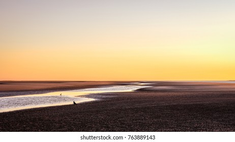 The sky nearly turns orange and the beach purple when the sun has almost set on a sunny late September day on the shores of the Wadden Island of Schiermonnikoog (Friesland, the Netherlands)