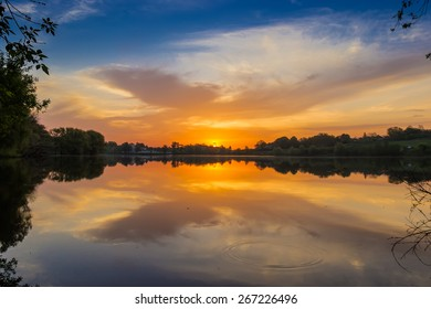 Sky with orange clouds reflected in the water of the lake, on the shores of which grow trees at sunrise. Rural landscape