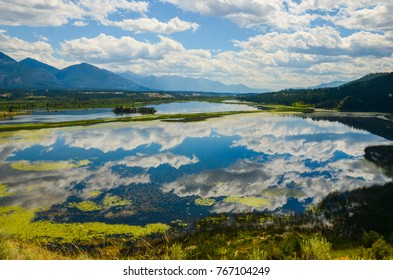 The sky reflected in the Columbia Wetlands in a mountain landscape near Invermere, British Columbia, Canada. The Rocky Mountains are to the east and the Purcell Mountains to the west.