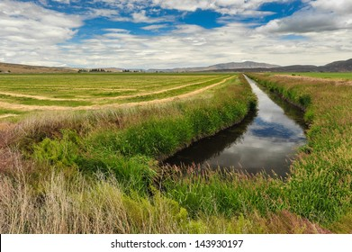 The sky is reflected in the water of an irrigation canal by a farm