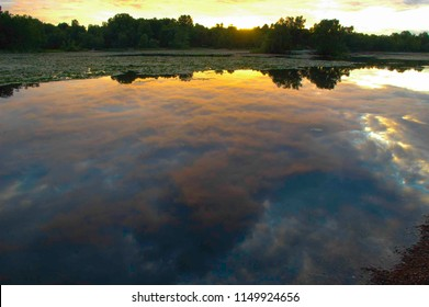 Sky reflection on Svarttemosse lake surface in summer midnight