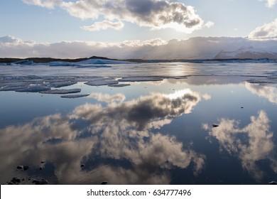 Sky reflection over Jakulsarlon lagoon, Iceland winter season landscape background