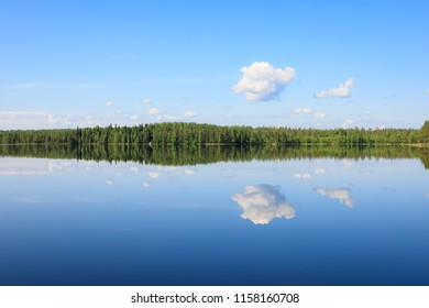 Sky reflects from still lake at summer day