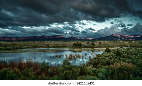 The sky and and shiny lake reflecting light while surrounded by the Utah landscape captured from the side of the road at dusk.