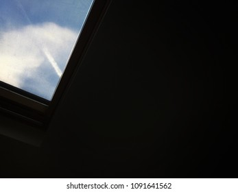 Sky through skylight window. Dark background with image on top left of blue sky with white cloud and vapour trail through lower right corner of a skylight window. Space to write text