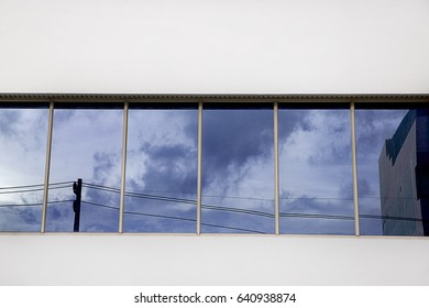 Sky view ,electricity post and building show on mirror window at building,