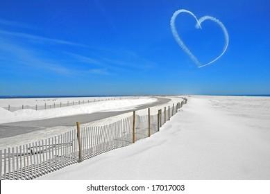 Sky writing heart over white sand on coastal island