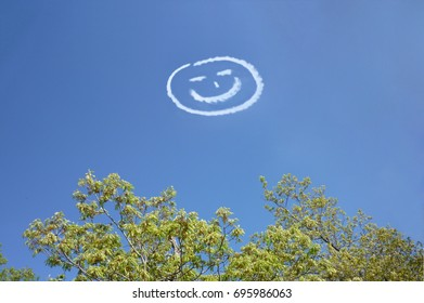 Sky writing in the shape of a happy face with blue sky and trees