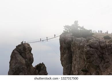 Skybridge, rope bridge on the Trident AI-Petri on a foggy morning. Silhouettes of tourists walking over the precipice. Crimea, Russia