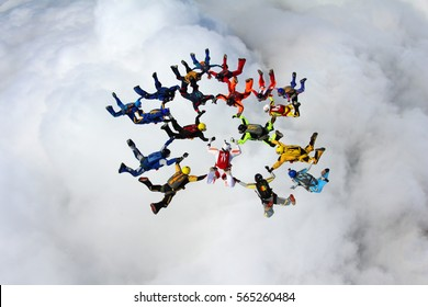 Skydive formation is flying above the white clouds.