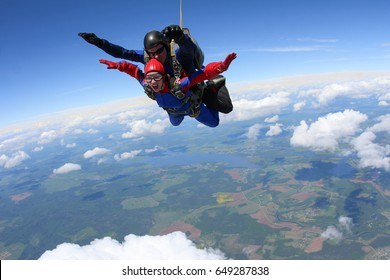 Skydive tandem is flying in the cloudy sky.