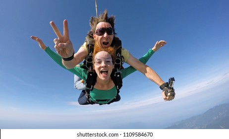Skydive tandem happiness couple over the sea