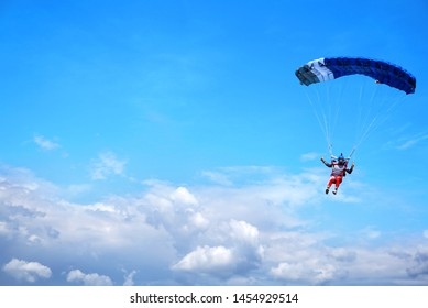 Skydiver with a blue little canopy of a parachute on the background a blue sky and white  clouds, close-up. Skydiver under parachute above the stormy clouds.  USA, Michigan