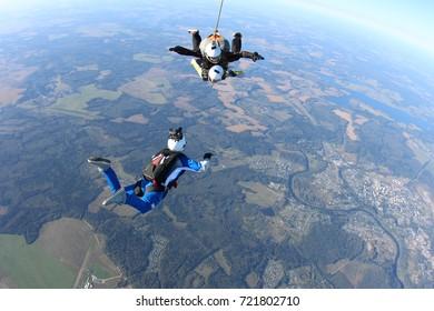 Skydiver cameraman is filming a tandem jump.