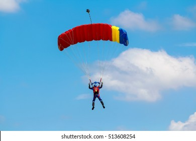 Skydiver and colorful parachute on the blue sky background