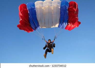 Skydiver controls the big parachute.