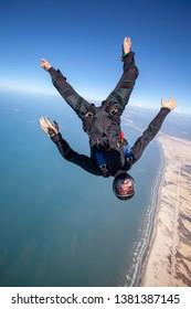 skydiver in free fall over brazilian beach