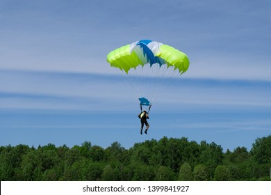 A skydiver is going to land.