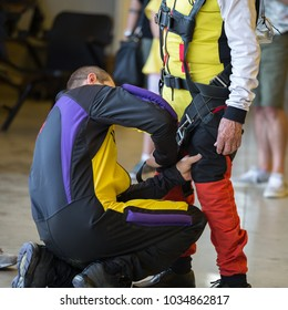 Skydiver Instructor Helps Apprentice to Tie Security Belt on His Parachutist Suit.