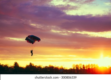 Skydiver On Colorful Parachute In Sunny Clear Sky. Active Hobbies