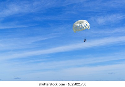 Skydiver on white parachute in sunny blue sky. Active lifestyle. Extreme sport.