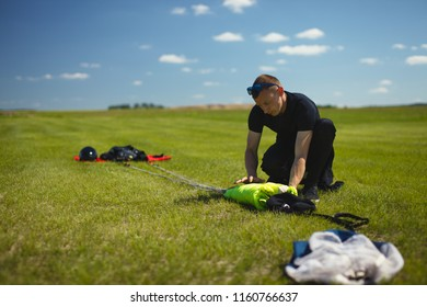 Skydiver and parachute canopy laid out on the grass during packing.