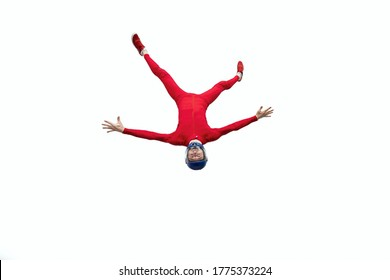 skydiver in a red suit flies head down, isolated on a white background. People jump with a parachute. Skydiving indoors.