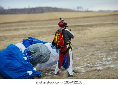 Skydiver stands in the field after landing with a parachute, close-up. Parachute jumps. Skydiving.