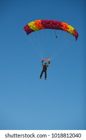 Skydiver under the canopy of the parachute against a blue sky on a sunny day. Parachute jumps.