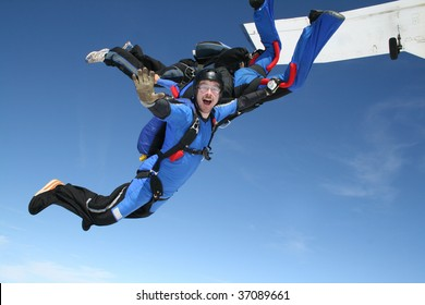 Skydiver waves at the camera