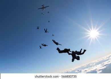 Skydivers are falling down from airplane into the blue sky.