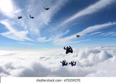 Skydivers Are flying above the white clouds.