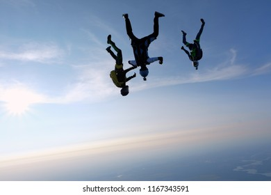 Skydivers in head down are in the sky.