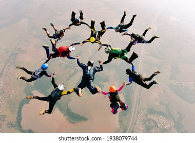 Skydivers holding hands making a formation. High angle view.