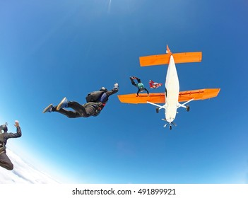 Skydivers jumping from the orange plane