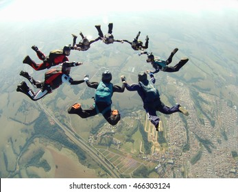 Skydiving friends holding hands
