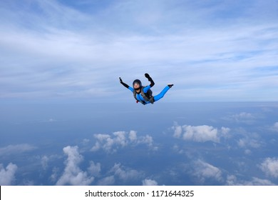 Skydiving. Girl in blue suit is in the sky.