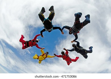 Skydiving holding hands friends