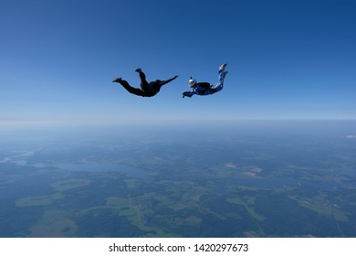 Skydiving. An instructor girl in a blue suit trains a student to fly.