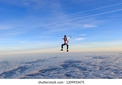 Skydiving. Man is sitting above sunset clouds.