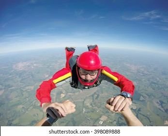 Skydiving senior man holding hands