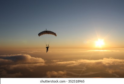 Skydiving sunset landscape of parachutist flying in soft focus