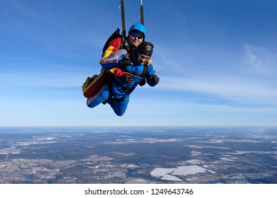 Skydiving. Tandem jump above snowy land.