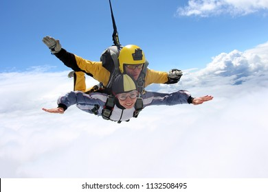 Skydiving. Tandem jump. Man and woman are flying in the sky.