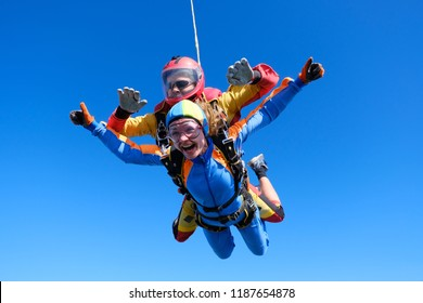 Skydiving. Tandem jump. Passenger is having fun.