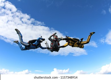 Skydiving. Two instructors are training a skydiver-student to fly.