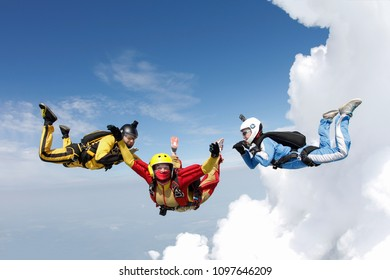 Skydiving. Two instructors are training a student in the sky.
